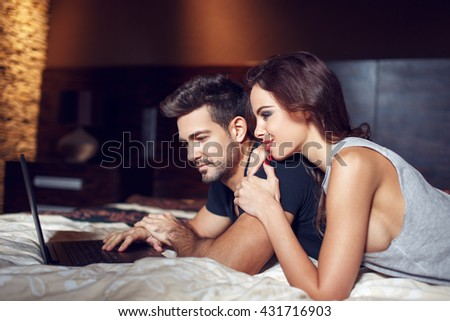 Young couple online shopping from bedroom, lying on bed #431716903
