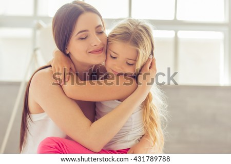 Beautiful young mother and her daughter are hugging and smiling while sitting with closed eyes on the bed at home #431789788