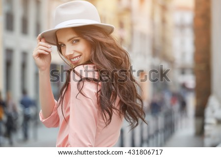 Close-up Fashion woman portrait of young pretty trendy girl posing at the city in Europe,summer street fashion,holding retro fedora hat popular until the 60s.laughing and smiling portrait.trendy #431806717