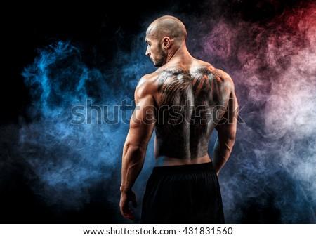 Back view of tattoed muscular man posing. Looking sideways #431831560