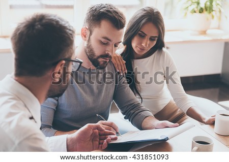 Paperwork before deal. Confident young man signing some document while sitting together with his wife and man in shirt and tie  #431851093
