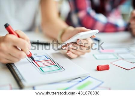 Closeup of designers creating mobile app prototype #431870338