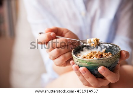 Young woman with muesli bowl. Girl eating breakfast cereals with nuts, pumpkin seeds, oats and yogurt in bowl. Girl holding homemade granola. Healthy snack or breakfast in the morning.. #431914957