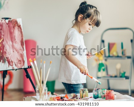 Cut girl painting in at her  home. Selective focus and small depth of field. Royalty-Free Stock Photo #431981110