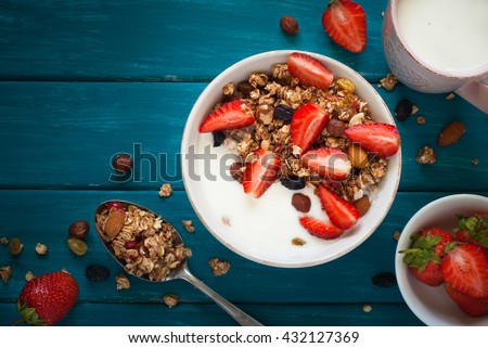 Granola. Granola with yogurt, honey and berries on blue wooden table. #432127369