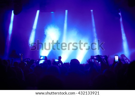 Cheering crowd in front of bright stage lights #432133921