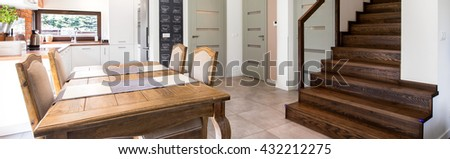 Part of a house with dining table and stairs. On the back is a kitchen #432212275