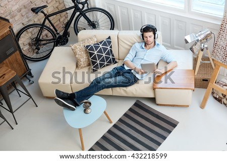 Young man relaxing on sofa, using tablet computer, listening to music at home. #432218599
