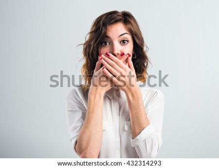 Pretty girl covering her mouth over grey background Royalty-Free Stock Photo #432314293