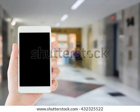 woman use mobile phone and blurred image of the elevator in the hospital