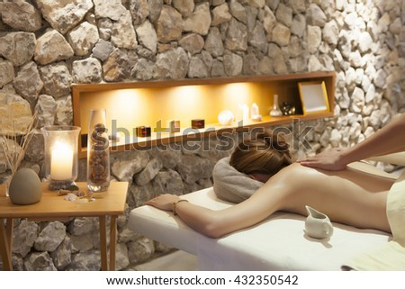 The woman enjoying massage treatment given by therapist #432350542