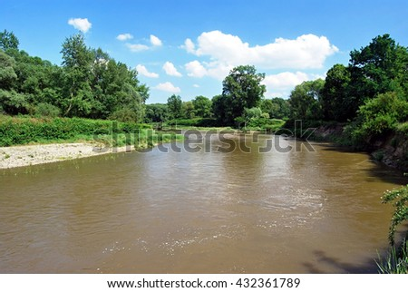 Odra river on czech-polish borders near Bohumin and Chalupki cities during spring day with blue sky and clouds Royalty-Free Stock Photo #432361789