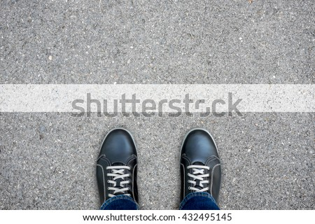 Black casual shoes standing at the white line making decision - stop and turn back or across the line and go further #432495145