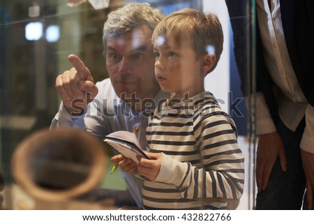 Father And Son Look At Artifacts In Case On Trip To Museum Royalty-Free Stock Photo #432822766