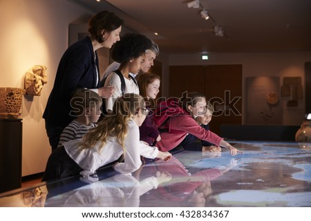 Pupils On School Field Trip To Museum Looking At Map Royalty-Free Stock Photo #432834367
