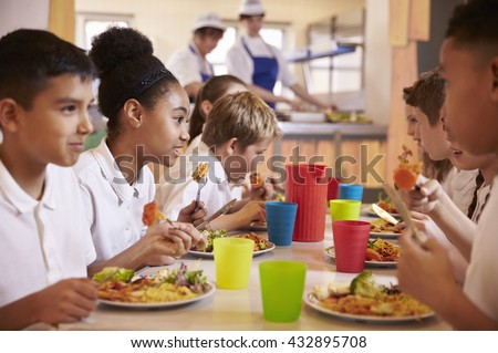 Primary school kids eat lunch in school cafeteria, close up Royalty-Free Stock Photo #432895708