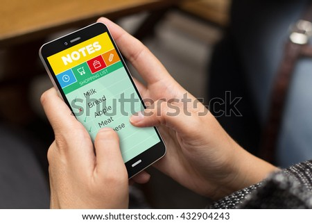Technology concept: girl using a digital generated phone to check a shopping list on note app. All screen graphics are made up. #432904243