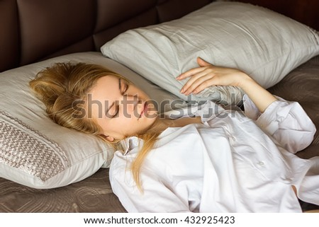 girl in a white men's shirt sleeping on the bed #432925423
