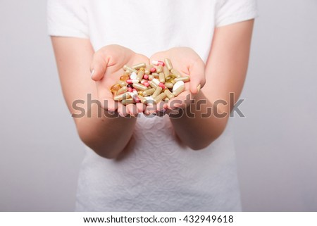 many pills and capsules in women in the hands #432949618