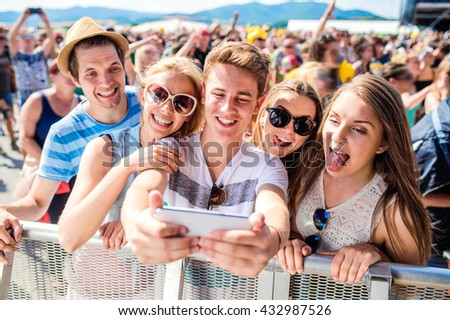 Teenagers at summer music festival in crowd taking selfie