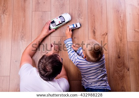 Unrecognizable father with his son playing with cars Royalty-Free Stock Photo #432988228