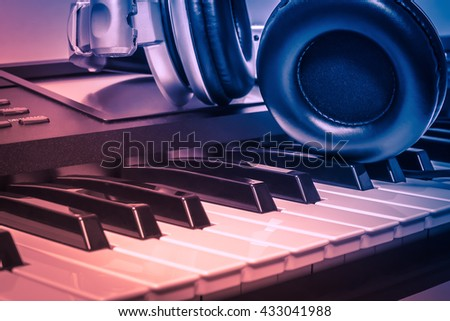 headphones on electric piano background by the  music instruments background. Royalty-Free Stock Photo #433041988
