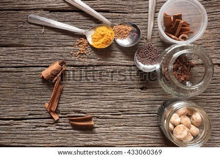 Fenugreek seeds, mustard seeds and turmeric powder on a spoon, with cinnamon, clove, candle nut in a jar over a wooden background  #433060369