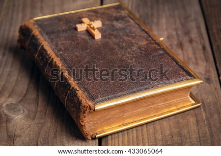 old closed holly Bible with wooden christian cross #433065064