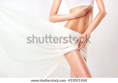 Perfect slim toned young body of the girl . An example of sports , fitness or plastic surgery and aesthetic cosmetology.   Royalty-Free Stock Photo #433091968