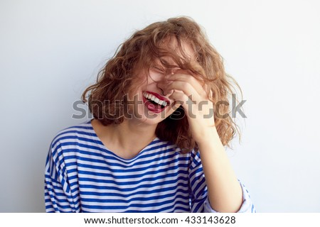 Laughing woman in marine shirt with curly hair over white wall. Toothy smile and red lips. Royalty-Free Stock Photo #433143628