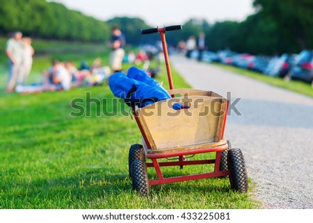 handcart for picnic standing at a meadow with people having a picnic in the blurred background Royalty-Free Stock Photo #433225081
