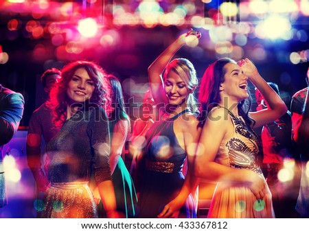 party, holidays, celebration, nightlife and people concept - happy friends dancing in club with holidays lights Royalty-Free Stock Photo #433367812