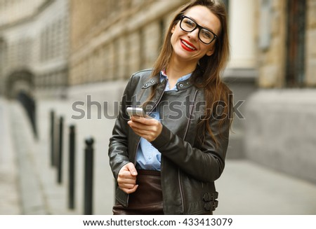 Businesswoman walking down the street while talking on smart phone. Happy smiling caucasian business woman busy #433413079