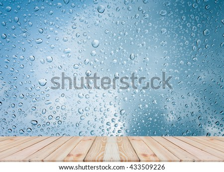 Wood table top on rain drops on clear window - can be used for display or montage your products #433509226