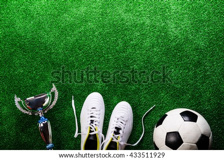 Soccer ball, cleats and trophy against green artificial turf #433511929