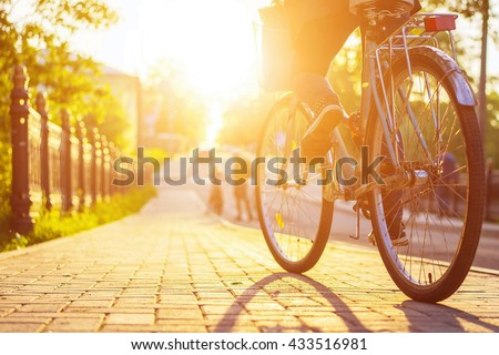 Bike at the summer sunset on the tiled road in the city park. Cycle closeup wheel on blurred summer background. Cycling down the street to work at summer sunset. Bicycle and ecology lifestyle concept. #433516981
