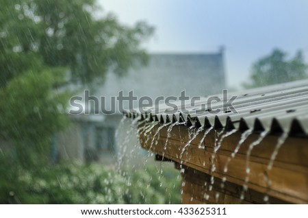 rain flows down from a roof down Royalty-Free Stock Photo #433625311
