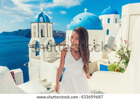 Santorini travel tourist woman on vacation in European destination walking on stairs. Asian girl in white dress visiting three blue domes in Oia village, greek island. Summer Europe holidays. #433699687