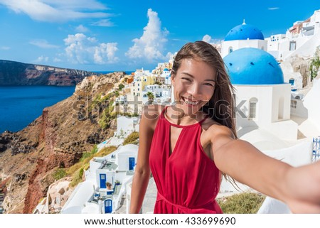 Europe travel selfie Asian woman in Oia village, Santorini. Cute happy smiling tourist girl taking self-portrait picture with smartphone during summer vacation in famous European destination, Greece.