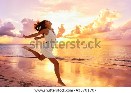 Freedom wellness well-being happiness concept. Happy carefree Asian woman feeling blissful jumping of joy on peaceful beach at sunset. Serenity, relaxation, mindfulness, stress free concepts. Royalty-Free Stock Photo #433701907