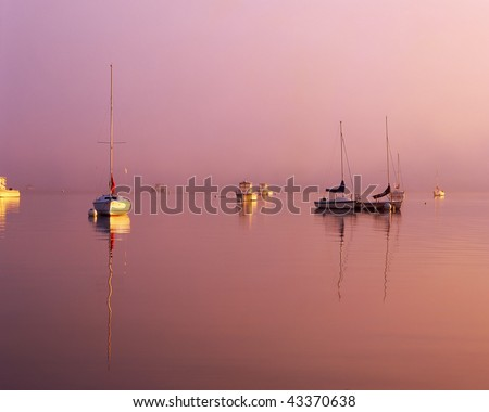 Brilliant sunrise cutting through the morning fog with sailboats at their moorings off the coast of New England #43370638