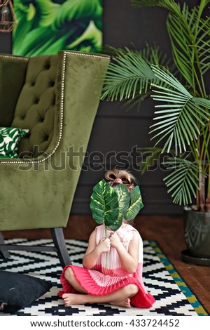 little girl in a beautiful dress covers her face with large leaves #433724452