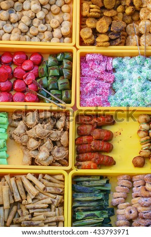 "Overhead shot over variety of delicious and colorful Malaysian home cooked local cakes or ""kueh"" sold at street market stall in Kota Kinabalu Sabah from top angle view with seller arranging the cake. #433793971"