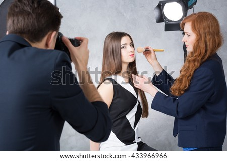 Female model posing for a photographer while having her makeup corected by a red-haired makeup artist