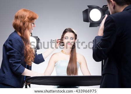 Young model having her strong makeup finished during shooting a portrait photo in a studio