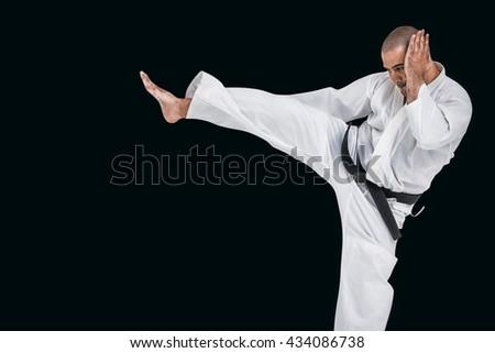 Fighter performing karate stance against black background #434086738