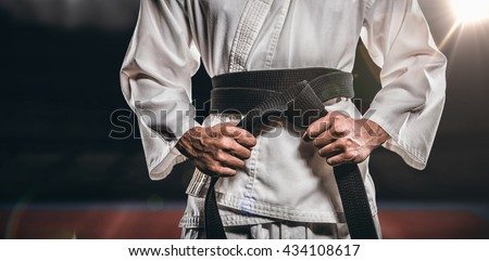 Fighter tightening karate belt against composite image of playing field indoor #434108617