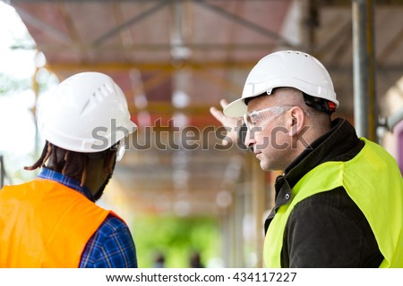 Two architects wearing hardhat and safety jacket pointing at scaffolding on construction site #434117227