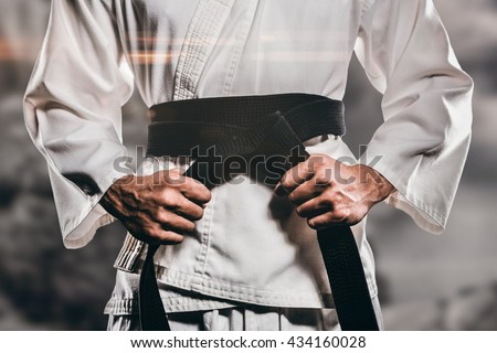 Fighter tightening karate belt against rock crashing down from cliff #434160028