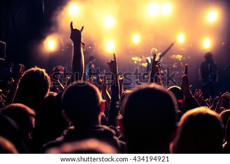 Rear view of an audience with hands raised at a music festival. High ISO #434194921